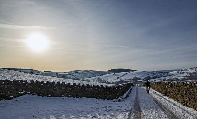 A cyclist on the snow at Blackmoss Reservoir in Barley, Pendle, Lancashire