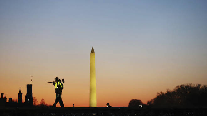 A construction worker carries a hammer at the National Mall in Washington DC (Biden Inauguration/AP)