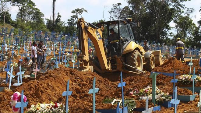 A bulldozer moves earth over a coffin in Manaus, Brazil (Edmar Barros/AP)
