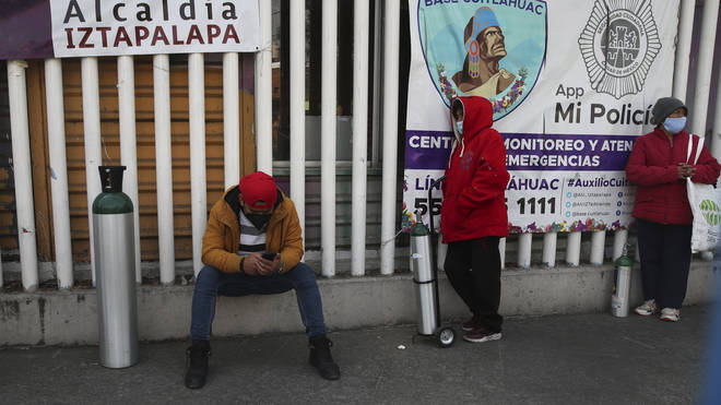 People wait their turn to fill their tanks with oxygen, in the Iztapalapa borough of Mexico City (Marco Ugarte/AP)