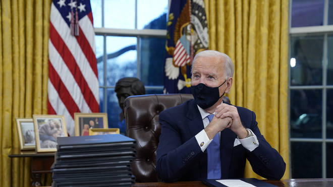 President Joe Biden waits to sign his first executive order in the Oval Office of the White House