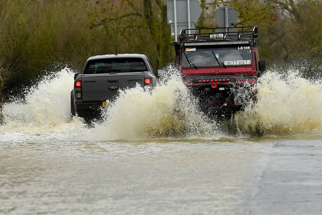 Cars drive through floodwater left by Storm Christoph