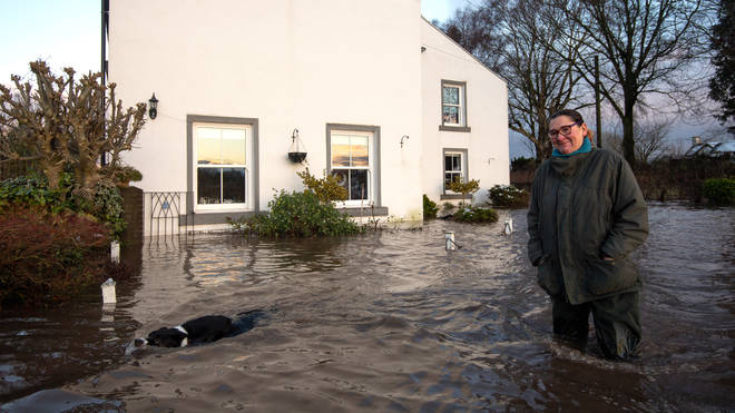 Ms Burns-Smith and her dog Tag outside their flooded home on the outskirts of Lymm in Cheshire