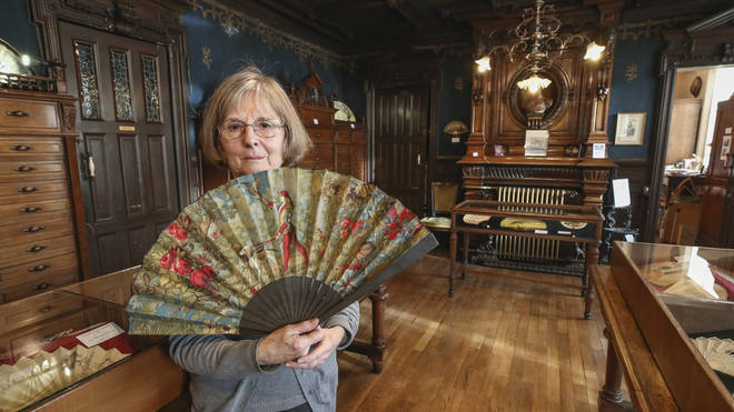 Anne Hoguet, 74, fan maker and director of the hand fan-making museum, poses with a a wood roasted hand fan representing the falcon hunt, gouache painting on paper dated from 1880 in Paris