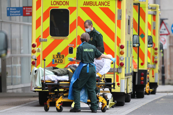 A patient is taken from an ambulance after being transferred to the Royal London Hospital in London