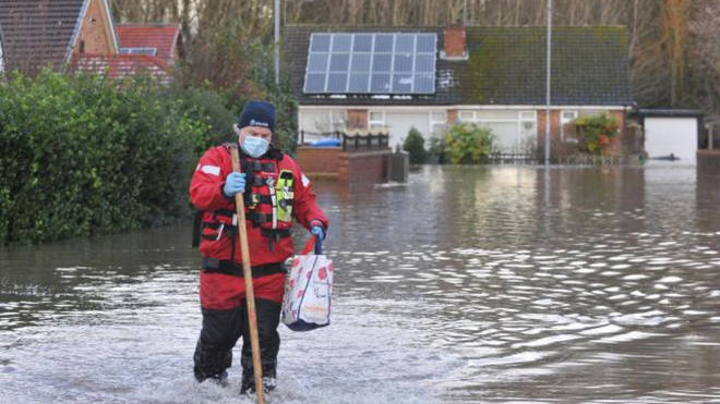Knutsford firefighter making his way through floodwater to assist with evacuation efforts in and around Cheshire