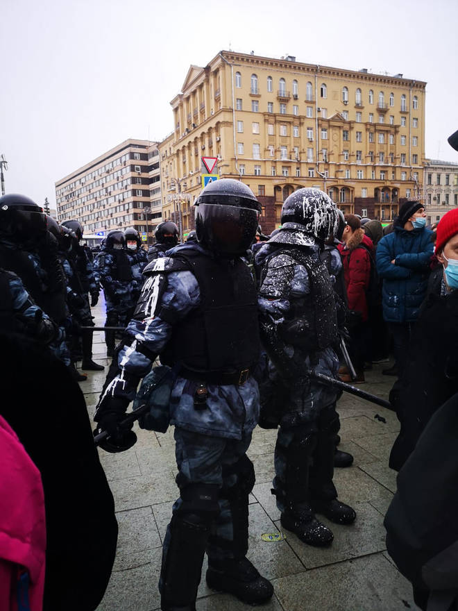 Police covered in what appears to be white paint during one of the protests in Russia