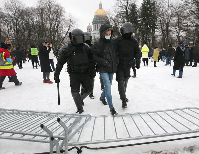 Riot police officers detain a participant in an unauthorized rally in support of Russian opposition activist in Senate Square, St Petersburg.