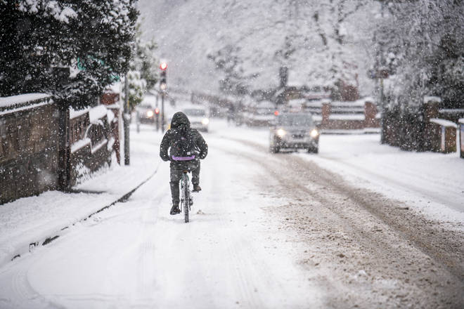 A man cycles through heavy snow in Worcester, Worcestershire on Sunday.