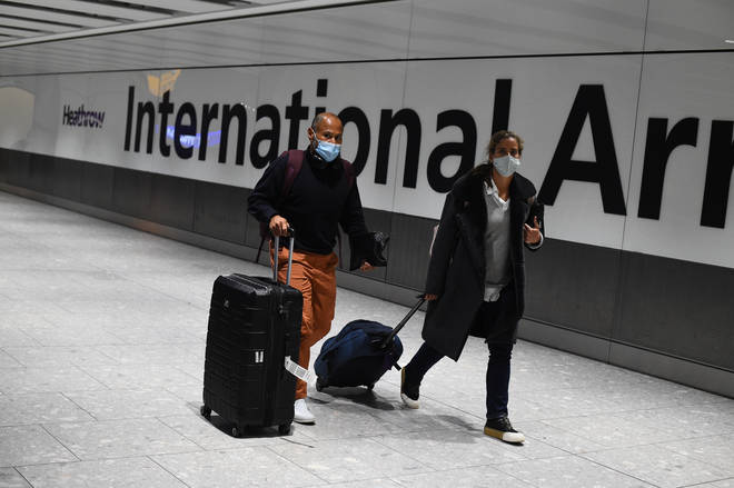 Passengers walk with luggage through the Arrival Hall of Terminal 5 at London's Heathrow Airport