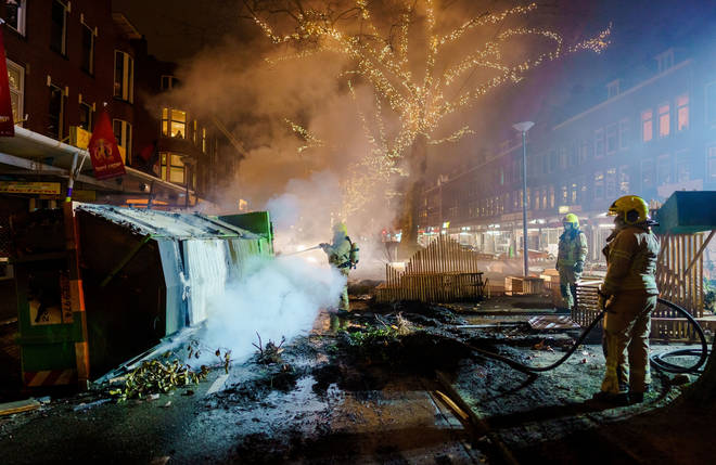 Firefighters work to extinguish a fire on the Groene Hilledijk in Rotterdam