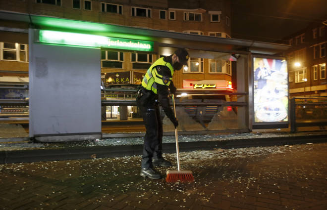 A police officer sweeps up glass from a bus stop that was smashed in protests against a nation-wide curfew in Rotterdam