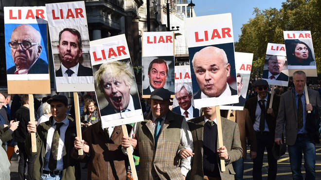 "Protesters hold up placards with the word ""liar"" written next to photos of prominent Brexiteers"