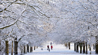 Families out walking during a snowy morning in Knighton Park in Leicester