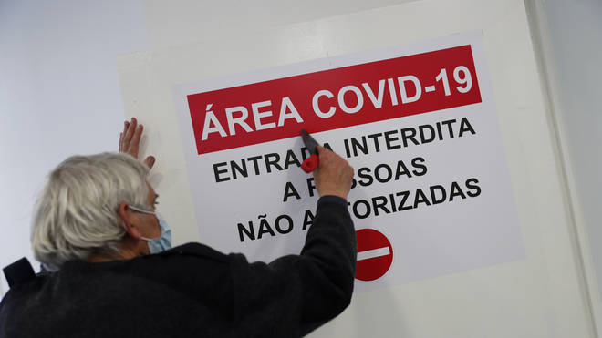 A worker puts up a sign on the door of a new Covid-19 ward being set up at the Military Hospital in Lisbon