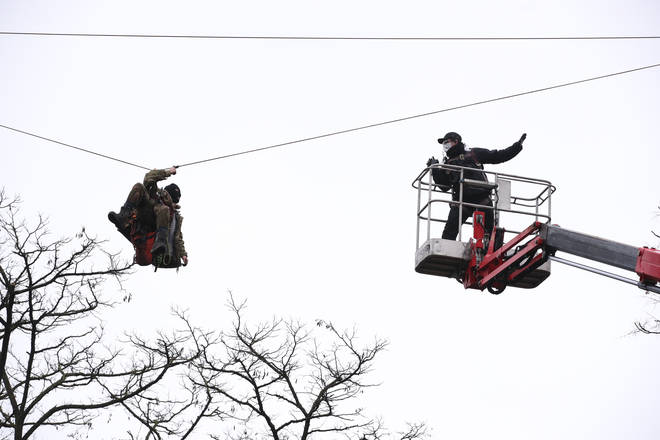 Enforcement officers used arial platforms to approach the protesters, one of whom was attached to a zip line between two trees.