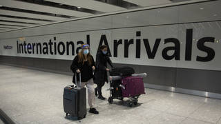 Passengers walk in the arrivals area at Heathrow Airport