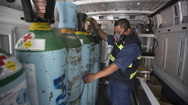 Health worker Jose Antonio Pena refills oxygen tanks for patients with Covid-19 in the Iztapalapa district of Mexico City