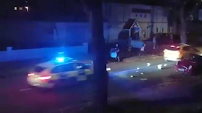 Thugs throw wheelie bins at a passing police car