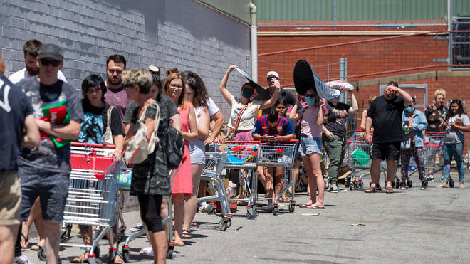 Long queues are seen outside a supermarket in Perth that was designated a potential exposure site