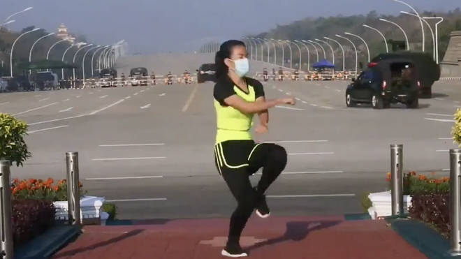 The woman dances as the coup appears to unfold behind her