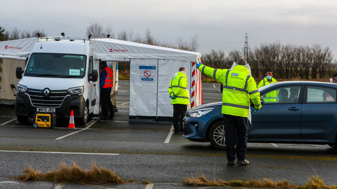 An NHS Test and Trace worker directs a car at a drive through testing centre in Southport, Lancashire