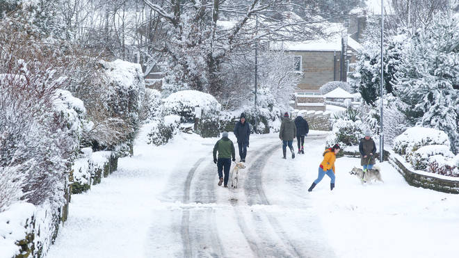 People walk along a snow-covered lane in West Yorkshire