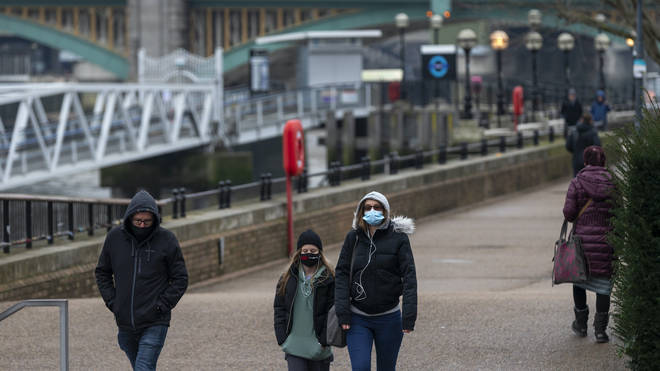 People wearing masks walk by the Thames in central London