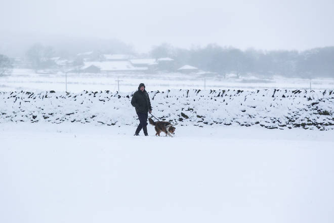 File photo: A man walks his dog across a snow-covered field in West Yorkshire