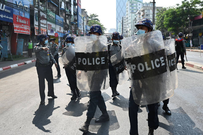 Riot police block a street as protesters gather for a demonstration against the military coup in Yangon