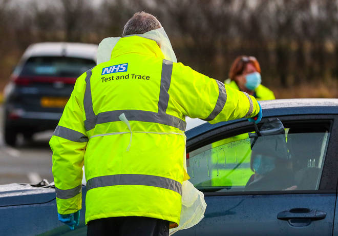 An NHS Test and Trace worker hands a person a test kit in a drive through testing centre in Southport, Lancashire