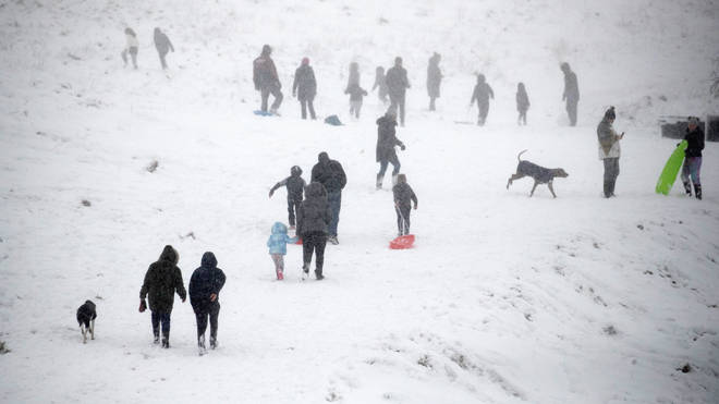 People enjoy the fresh snow in Wye National Nature Reserve near Ashford in Kent