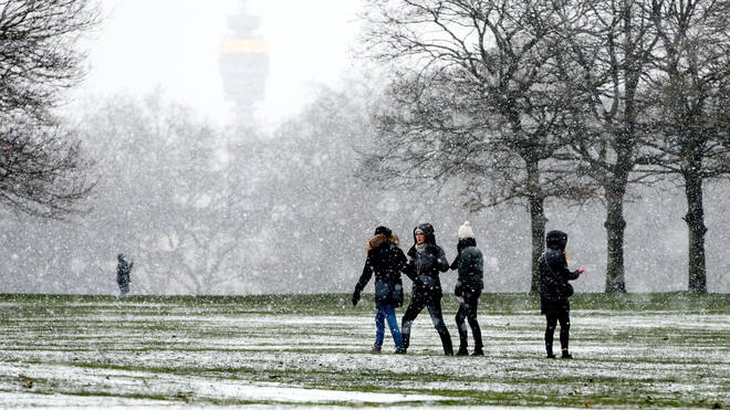 People walk through Storm Darcy snowfall in Hyde Park in London