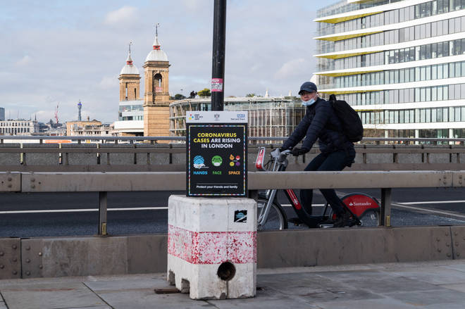 A cyclist rides past a coronavirus prevention poster on London Bridge as England remains under third lockdown