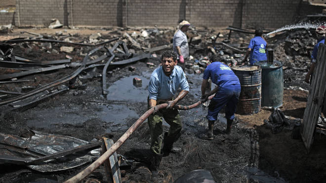 Workers use a water hose to put down a fire at a vehicle oil store hit by Saudi-led airstrikes in Sanaa, Yemen.