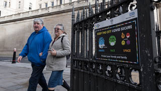 People wearing plastic visors walk past a coronavirus prevention poster in the City of London as England remains under third lockdown