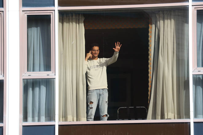 Roger Goncalves, who is from Brazil and travelled via Madrid to get to the UK, waves from the window of Radisson Blu Edwardian Hotel