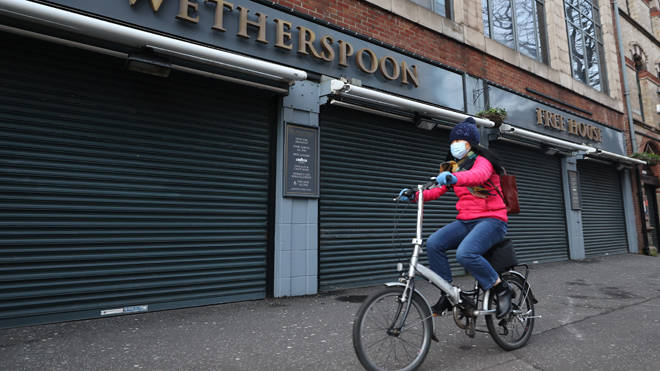 A woman cycles past a closed pub in Belfast during Northern Ireland's lockdown