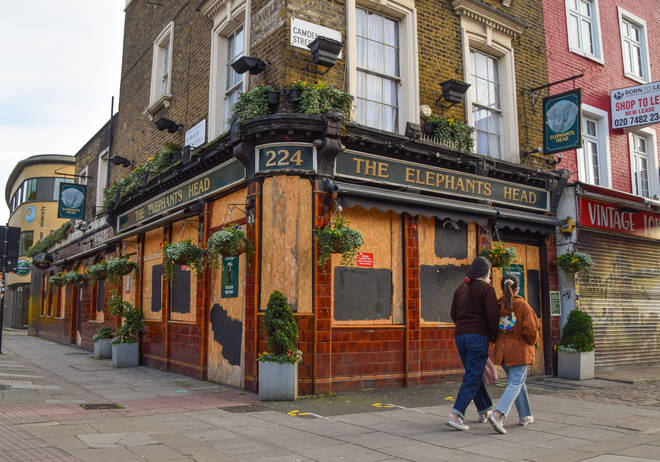 A couple walking past a closed pub in Camden