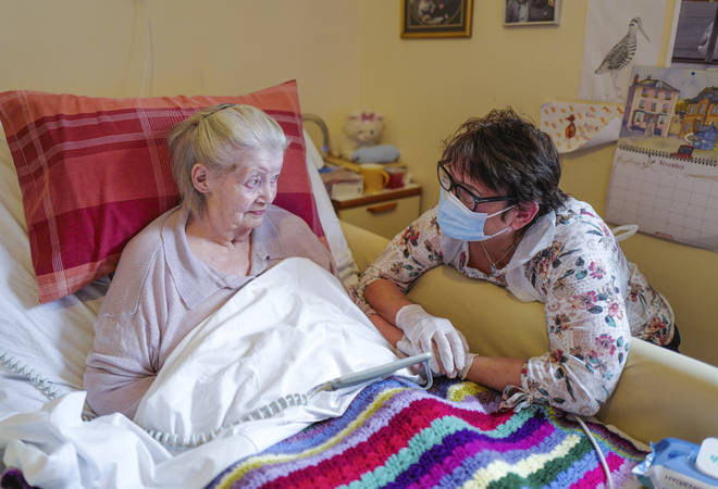 File photo: Care home resident Dot Hendy holds her daughter Louise's hand for the first time since March after Louise successfully passed a Rapid Covid-19 Test