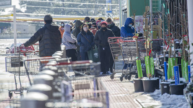 Shoppers queue for food outside a Texas supermarket during the big freeze