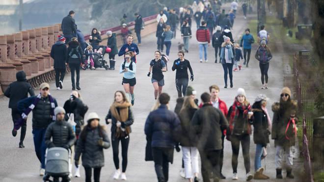 People walk and run through Battersea Park, London, during England's third national lockdown