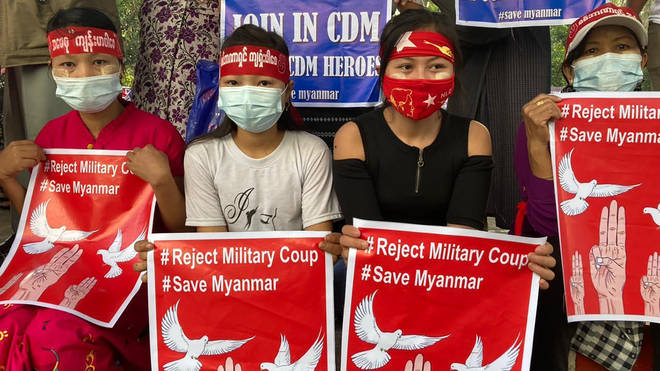 """Anti-coup protesters hold posters that read """"#Reject Military Coup #Save Myanmar"""" as they gather in Yangon on Monday"""