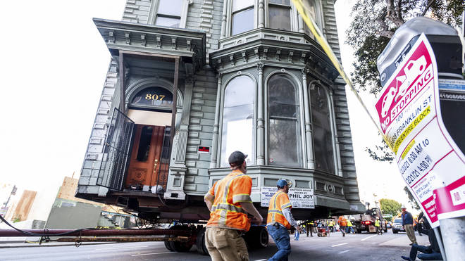 A Victorian house is moved through the streets
