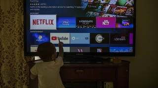 A child touches a TV screen