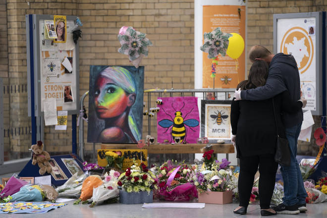 People grieve at a memorial of the Manchester Arena attack