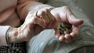An elderly woman with loose change in her hands