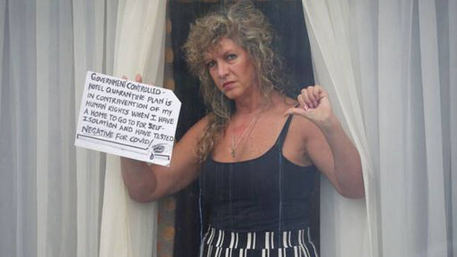 A quarantined traveller holds a sign up to the window of her room.