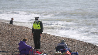 A community support officer speaks to people enjoying the sunshine on Brighton beach in Sussex on Sunday.