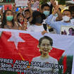 Migrant workers from Myanmar flash the three-finger protest gesture while they hold banners with images of deposed Myanmar leader Aung San Suu Kyi before participating in a march by Thai pro-democracy activists in Bangkok on Sunday